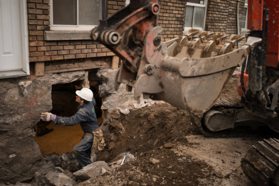 A worker checking the structure before continuing the destruction of the foundation