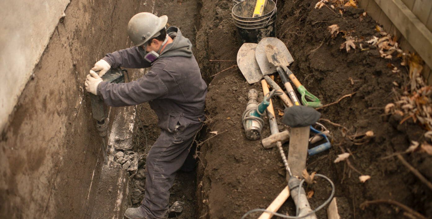 Worker breaking the footing to install steel piles