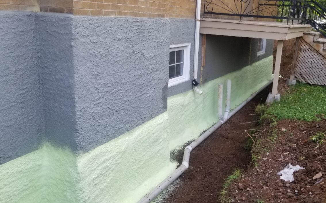 A brand new foundation showcasing the waterproofing membrane and proper drainage
